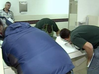 City inspectors check faucets in a hotel bathroom on Tuesday, March 11, 2008.