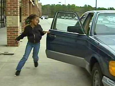 Imani Williams, 9, reenacts running from a parked car outside a Dollar General Store near McGee's Crossroads. She and her mother, Pauline, say a man tried to abduct Imani, who had been left unattended in the car.