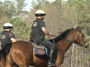 Police officers ride on horseback at Lake Lynn Park.