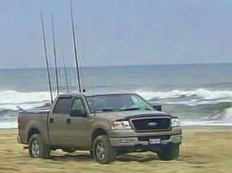 A fisherman accesses to remote areas of the Cape Hatteras National Seashore by driving his truck on the beach.