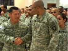 Spc. Vivek Mishra (right) with the 101st Airborne Division, shakes hands with Pfc. Henry Michael, 72nd Military Police Company, during a naturalization ceremony held April 12 at the Al Faw Palace, Camp Victory, Iraq. The Soldiers were part of a group of 259 servicemembers, representing 71 countries, who gained their citizenship.  (U.S. Army photo by Staff Sgt. Jeremy D. Crisp/MNC-I PAO)