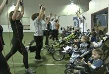 Moms work their arms as their kids watch during a Stroller Fit class.