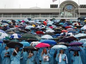 Seniors huddled underneath umbrellas as light rain fell at the University of North Carolina at Chapel Hill's graduation ceremony on Sunday, May 11, 2008. (Photo by Jerome Carpenter)