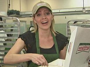 WRAL Reporter Kim Dean tries to carefully get doughnuts from the conveyor belt into the box without damaging them.