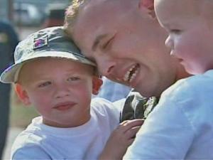 Sgt. Matthew Hall hugs his 2- and 4-year-old sons at a homecoming ceremony for the 1332nd Military Police Company at the Rocky Mount-Wilson Airport on Tuesday, June 10, 2008.