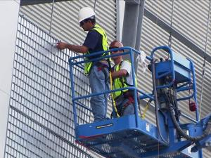 A crew installs panels on the $1 million shimmer wall on the side of the new Raleigh Convention Center, which opens in September.