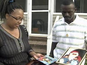 Tracey and Tony Hickson show pictures of their twin sons, who defeated a backyard gate and nearly drowned in a swimming pool on Sunday, June 22, 2008.