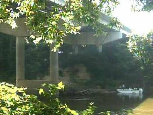 Rescue crews work to retrieve human remains found in a ravine under the Grove Street bridge in Fayetteville on July 18, 2008.