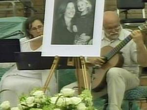 A flautist and guitarist perform behind a picture of Nancy Cooper and her daughter Bella at a public memorial service in Cary Koka Booth Amphitheatre on Saturday, July 19, 2008.