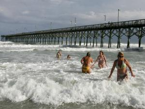 Robin Heath, right, from Pink Hill, N.C., walks out of the surf after swimming by the Surf City Pier in Surf City, N.C. late Saturday afternoon July 19, 2008.  Dark clouds are slowly approaching from the south in the background as Tropical Storm Cristobal forms off the coast.  (AP Photo/Don Bryan)