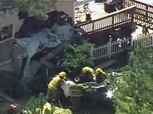 Crews work to remove a car that crashed into a house on Cottage Way in Fayetteville from the crash site.