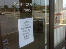 A closed sign hangs on the door of Swift Creek Insurance and Realty Monday following a raid by agents from the North Carolina Department of Insurance.
