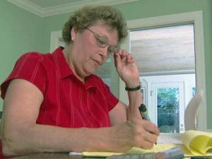 Beverly Moriarty checks over her pay stubs.