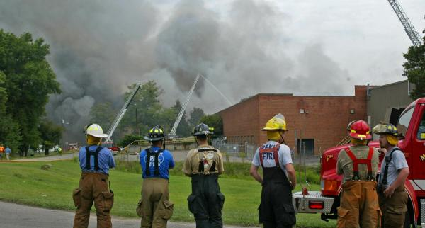 Firefighter take a break to watch fellow firefighters battle the multi-alarm fire at the former Milliken textile plant that burned for more than seven hours on Sunday, August 17, 2008. No one was injured as firefighters from more than 20 departments assisted the local fire department. (Photo by Thomas Babb)