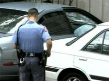 A Raleigh police officer examines a car that rammed into an apartment building off New Bern Avenue on Aug. 22, 2008.
