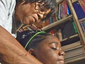 Deryl von Williams, founder of the alternative Vance County Learning Center, leans over to help a student.