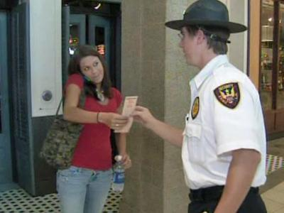 A mall security guard at the Triangle Town Center hands a flyer explaining the mall's new Youth Escort Policy to a shopper on Sept. 19, 2008.
