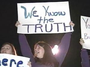 """Friends of a missing Granville County mother stand outside her husband's parents' house chanting: """"Bring Kelly home,"""" """"Why lie to the SBI?"""" and """"Don't be scared of Nancy Grace."""""""