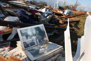 A family photo album lies in storm debris where Joshua Wiggins, 11, was found at his grandparents' collapsed home at 3850 London Church Road in Wilson County.