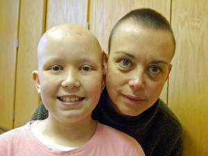 Emily Beamer, 11, smiles alongside her mother, Malinda Beamer. Malinda shaved her head to support Emily, who battled a brain tumor.