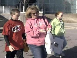 Carolina Hurricanes fan Kelley Burriss, center, leaves the RBC Center after buying some team merchandise Wednesday.