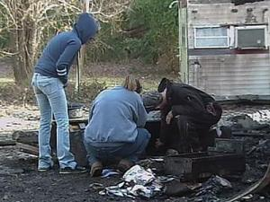Family members sift through the remnants of a house fire that killed Joseph Wiggs and Hilda Allen.