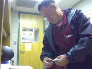 In this Web cam image from Dec. 8, 2008, Harold Jones holds what appears to be a pack of chewing gum from Paula Parrish's desk.