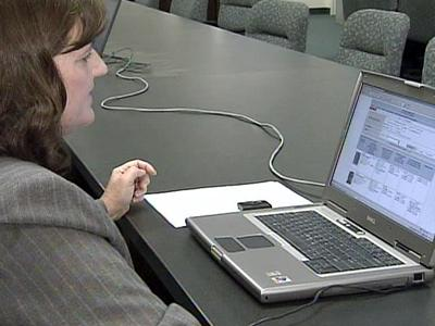 Cindy Cousins, an applications systems manager with the Department of Correction, uses an online system to track offenders.