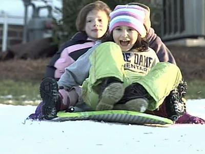 Children on Chrismill Lane in Holly Springs slide down a man-made slope on Dec. 31, 2008. Parents paid to get three tons of snow delivered to the neighborhood.