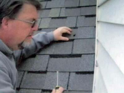 Joe Kent removes a bullet from the roof of his Franklin County home. (Image from Jackie Kent)
