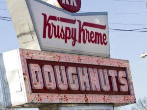 Runners mingle beneath the sign at Krispy Kreme.