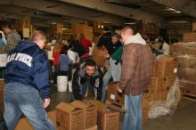 Around 220 Seymour Johnson Air Force Base service members and their families gathered at the MERCI Mission Center in Goldsboro to pack food for needy civilians in Afghanistan Saturday, March 14, 2009. The nonperishable food will be distributed through local schools by the United Methodist Church and the Trust in Education nonprofit.