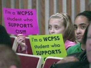Wake County students hold up signs to show their support for the Community in Schools program, which offers tutoring and academic support to hundreds of economically at-risk students. The students attended a meeting of the Wake County Board of Education, which is considering cuts to the program.