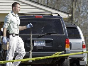 An investigator carries a weapon at the scene where a gunman opened fire at a nursing home Sunday morning, killing at least six people and wounding several others in Carthage, N.C., Sunday, March 29, 2009. The gunman was also injured before he was apprehended by police after the 10 a.m. shooting at Pinelake Health and Rehab, Police Chief Chris McKenzie told several television stations. A police officer was also hurt. (AP Photo/Gerry Broome)