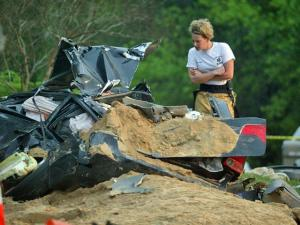 A Cary EMS worker looks at the mangled wreck of a Honda Civic in which Kara Walden Benton, 25, of Holly Springs, was pinned Monday, April 13, 2009, on Davis Drive after a dump truck carrying sand and gravel overturned on the car. The car driver was airlifted to Wake Med in Raleigh. (Photo by Thomas Babb)