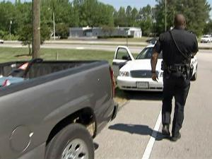 A Garner police officer returns to his cruiser after a traffic stop. A U.S. Supreme Court ruling limits searches of vehicles during such stops.