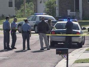 Raleigh police officers question residents at the scene where a man's body was found lying face-down on Corydon Court in the Battle Ridge at Chastain community, off Barwell Road, early Tuesday, May 12, 2009.