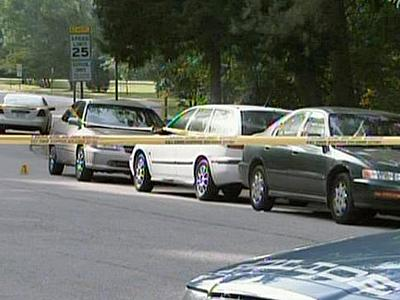 Raleigh police officers block off Bertie Drive and Culpepper Lane, where they believe shots were fired into vehicles the morning of Friday, May 22, 2009. Students at Enloe High School park their cars along the streets.