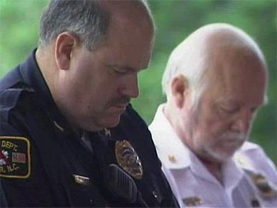 Garner Police Chief Thomas Moss, left, and Garner Fire Chief Phil Mitchell bow their heads during a June 16, 2009, moment of silence to remember those killed and injured in an explosion at a ConAgra Foods plant in Garner.