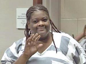 Carletta Patrice Alston, 24, smiles and waves to her family during her first court appearance on first-degree murder charges in the death of her stepfather, Knightdale minister Michael Donnell Smith on Thursday, June 18, 2009.