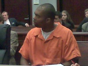 Samuel James Cooper sits with his attorneys during a July 10, 2009, status hearing. Cooper is the suspect in a string of homicides dating to May 2006.