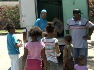 Volunteers hand out bagged lunches to children as part of the Inter-Faith Food Shuttle's Backpack Buddies Program on July 24, 2009.