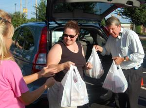 WRAL Anchor David Crabtree helps Heide Cassimatis unload bags of groceries, which she donated for the BackPack Buddies food drive on Aug. 20, 2009.