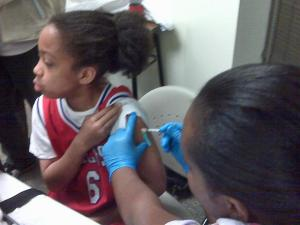 A health-care worker gives an H1N1 flu vaccine to a girl at a free clinic in Wake County on Monday, Oct. 19, 2009.