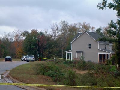 Police tape surrounds a burned home on Cameo Court in the Chandler's Ridge subdivision, off Glen Laurel Road, in Clayton.