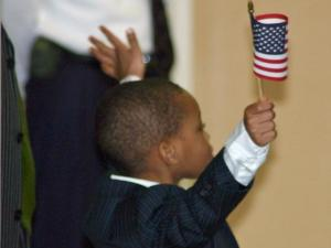 A young boy throws up his arms and the American flag in celebration after the new citizens take their oath on Friday, Jan. 22, 2010. (Photo by Bill Burch)