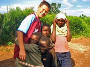Evan Holland (left) is hugged by orphans in Kaihura, Uganda. Evan was part of a youth summer mission trip organized by the Wake Forest-based charity Embrace Uganda. (Photo courtesy of Embrace Uganda)