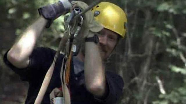Joel Hoffman, one of the designers of the ZipQuest course in Fayetteville, goes for a trip along one of its zip lines.