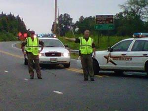 Durham County deputies direct traffic away from the area where a road crew found a body on June 30, 2010.