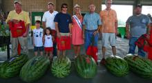 North Carolina Watermelon Queen Madeline Varner poses with the entrants in the Biggest Watermelon weigh-off: (left to right) Larry Boyette, 170.5 pounds, third place; Donald Murphy, 184 pounds, first place; Robert Ward, 153 pounds, fifth place; H.C. Williams, 168.5 pounds, fourth place; Charles Payne, 136.5 pounds, sixth place; and Jimmy Briggs, 180 pounds, second place.